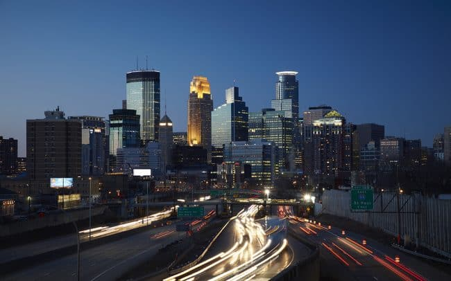 Cityscape photograph showing the Minneapolis skyline at dusk driving north on I 35W. Photographed by Sioux Falls SD based commercial photographer Paul Heckel of Heckel Photography.