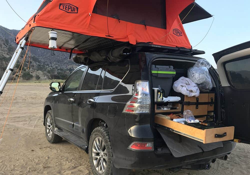 Photograph of SUV with Tepui Kukenam 3 Rooftop Tent mounted to top.
