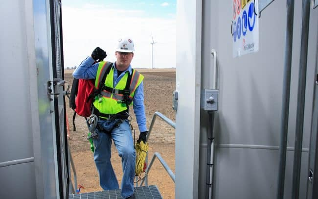 Photograph of worker entering wind tower for advertising photographed by Sioux Falls based commercial photographer Paul Heckel of Heckel photography.